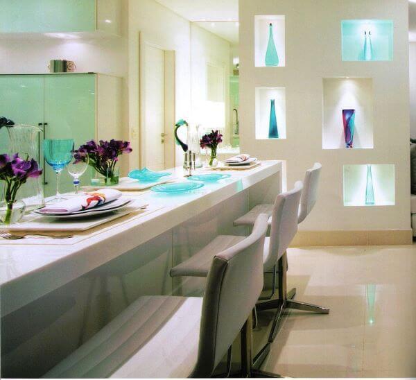 Sala de jantar com estante de gesso e iluminação nos vasos decorativos