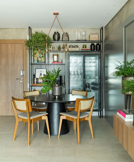 Sala de jantar estilo industrial com mesa cone preta e cadeiras de madeira