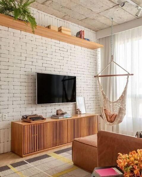 Sala pequena com rack rustico e cadeira de balanço