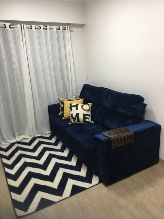 Sala pequena com sofá azul marinho e tapete chevron