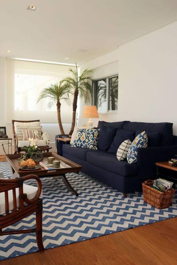 Tapete chevron em tons de azul e sofá azul marinho com móveis de madeira na sala