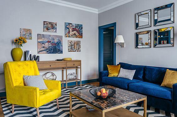 Tapete chevron na sala com sofá azul e poltrona amarela