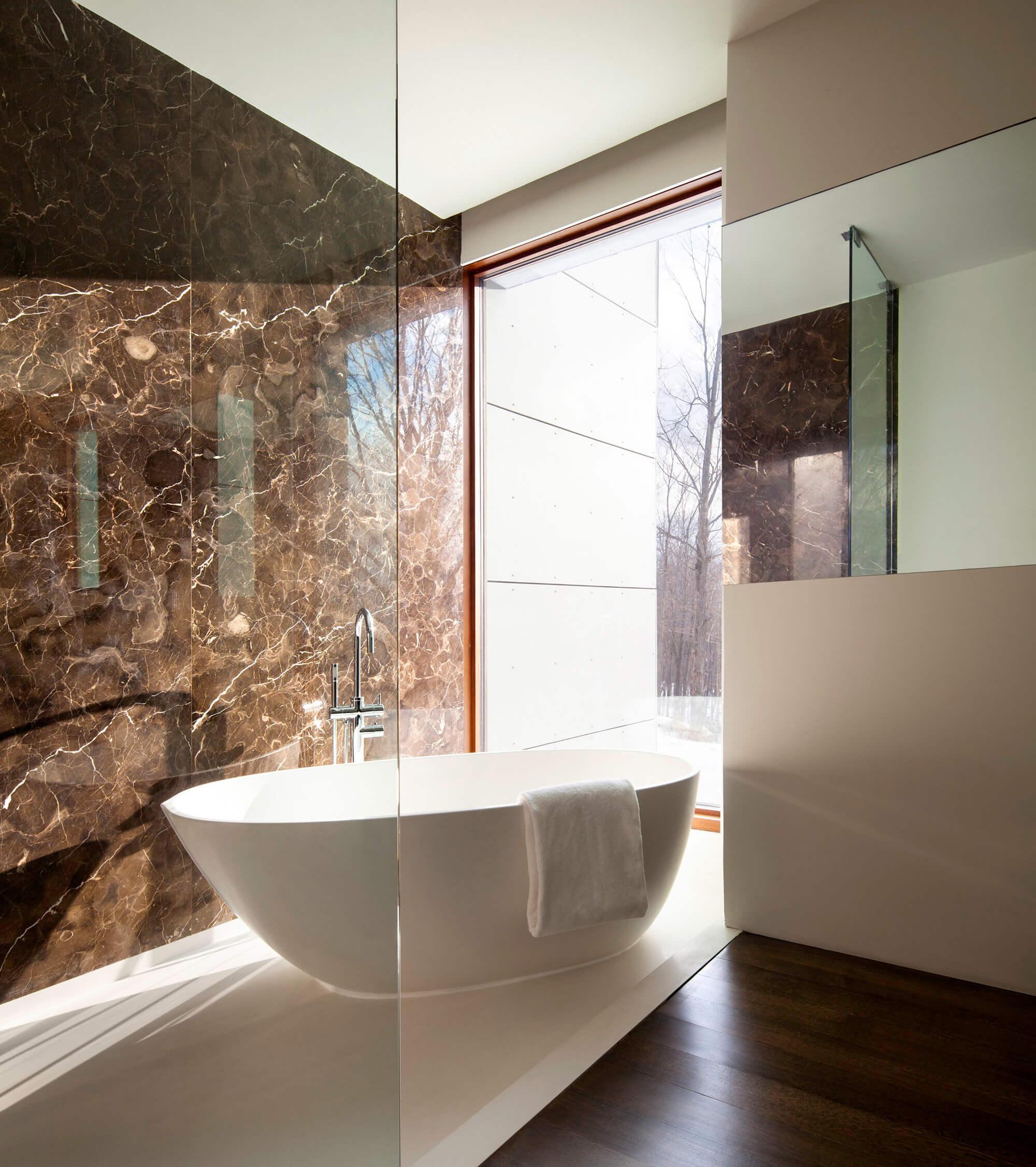 Tons de marrom para banheiro moderno com piso de madeira e banheira branca