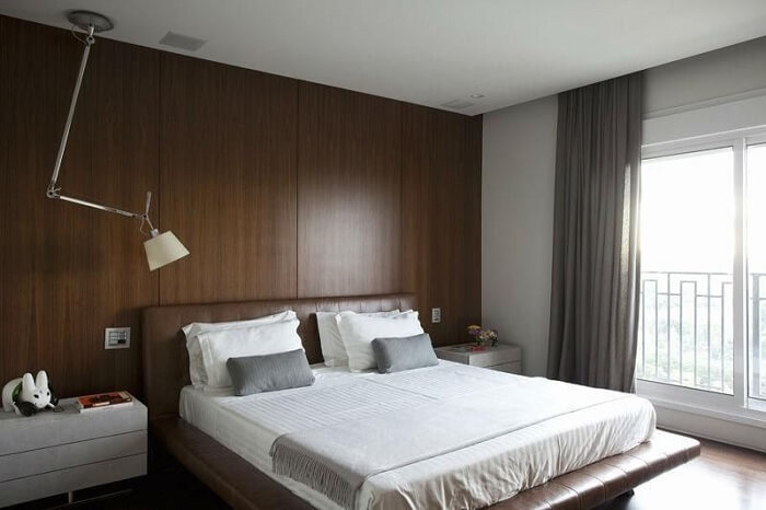 Quarto marrom: parede com painel de madeira e criado mudo branco. Projeto de Triplex Arquitetura