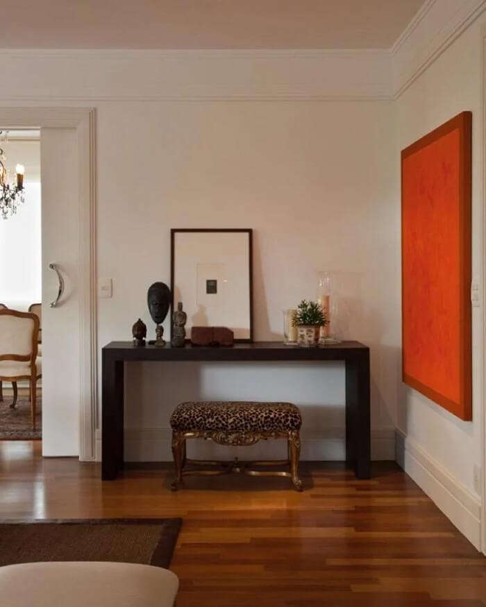 Use um modelo simples de aparador preto caso queira destacar objetos decorativos. Projeto de Fernando Piva Interiores