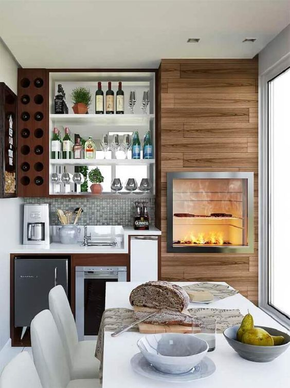 Varanda com churrasqueira gourmet de parede com revestimento de madeira