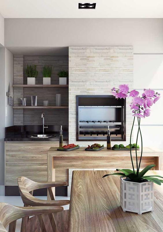 Varanda com churrasqueira gourmet de parede e revestimento tijolinho e móveis de madeira para área externa