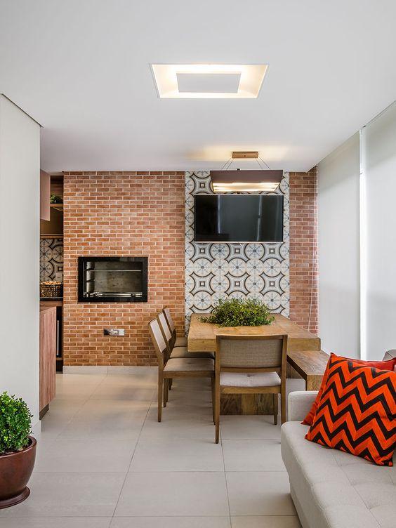 Varanda com churrasqueira gourmet de parede e tijolo