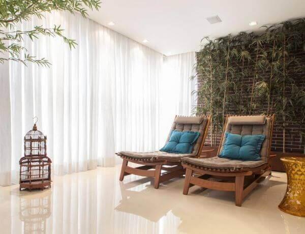 Varanda com piso bege de porcelanato e espreguiçadeiras confortáveis