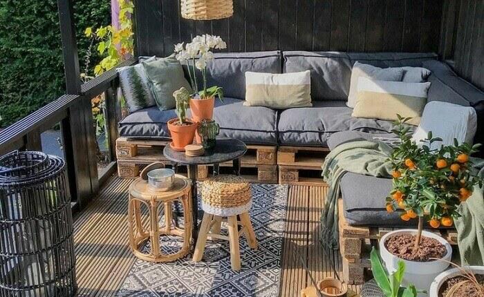 Sacada decorada com sofá de palete e almofadas cinza