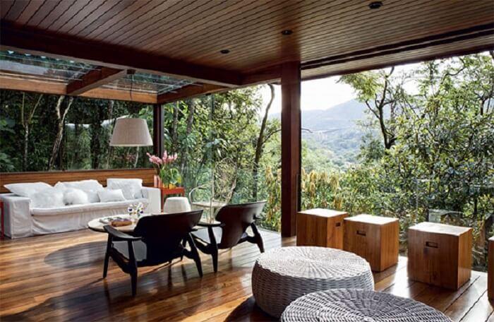 Sacada de madeira com guarda corpo de vidro para aumentar a vista do jardim