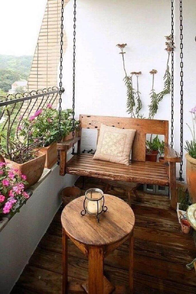 Sacada de madeira com balanço de madeira e floreira