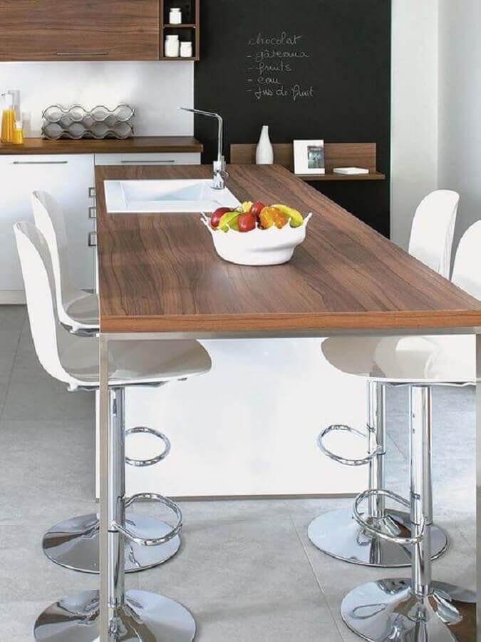 cozinha com ilha de madeira decorada com banqueta giratória branca Foto Micasa Revista