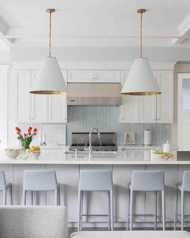 cozinha com ilha decorada com luminária grande e banqueta branca estofada Foto Home Fashion Trend