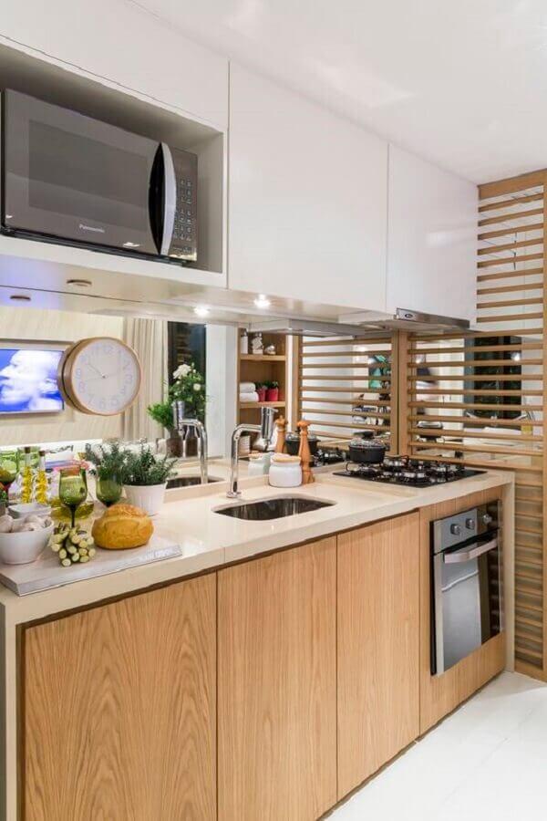 cozinha decorada com gabinete de madeira e armário suspenso branco com nicho para microondas Foto Jeito de Casa