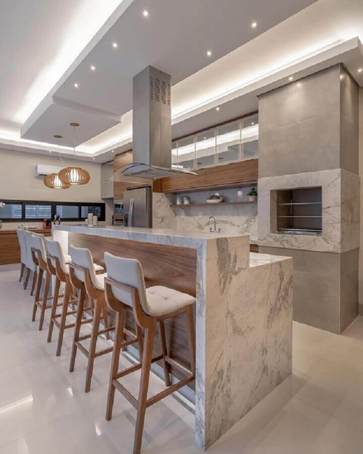 Decoração de área gourmet com churrasqueira e bancada de mármore