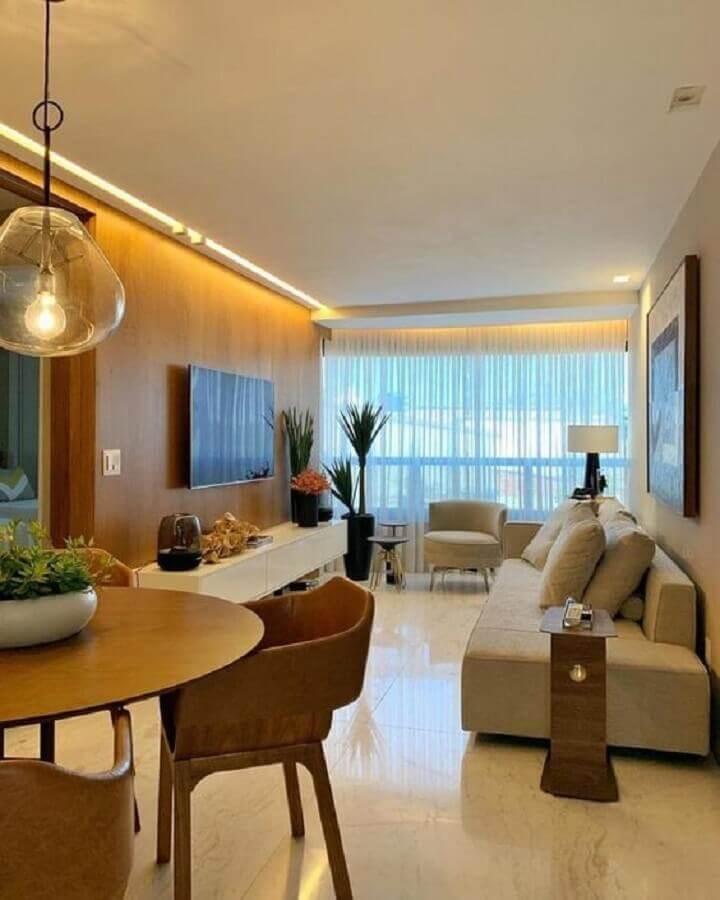 decoração de sala de apartamento em cores neutras com painel de madeira para TV Foto Iluminim LED