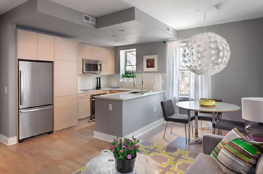 decoração em tons de cinza com armários de madeira para cozinha americana com sala de jantar e estar integrada Foto Arquidicas