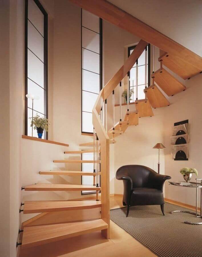escada de madeira interna decorada com poltrona preta embaixo Foto Pinterest