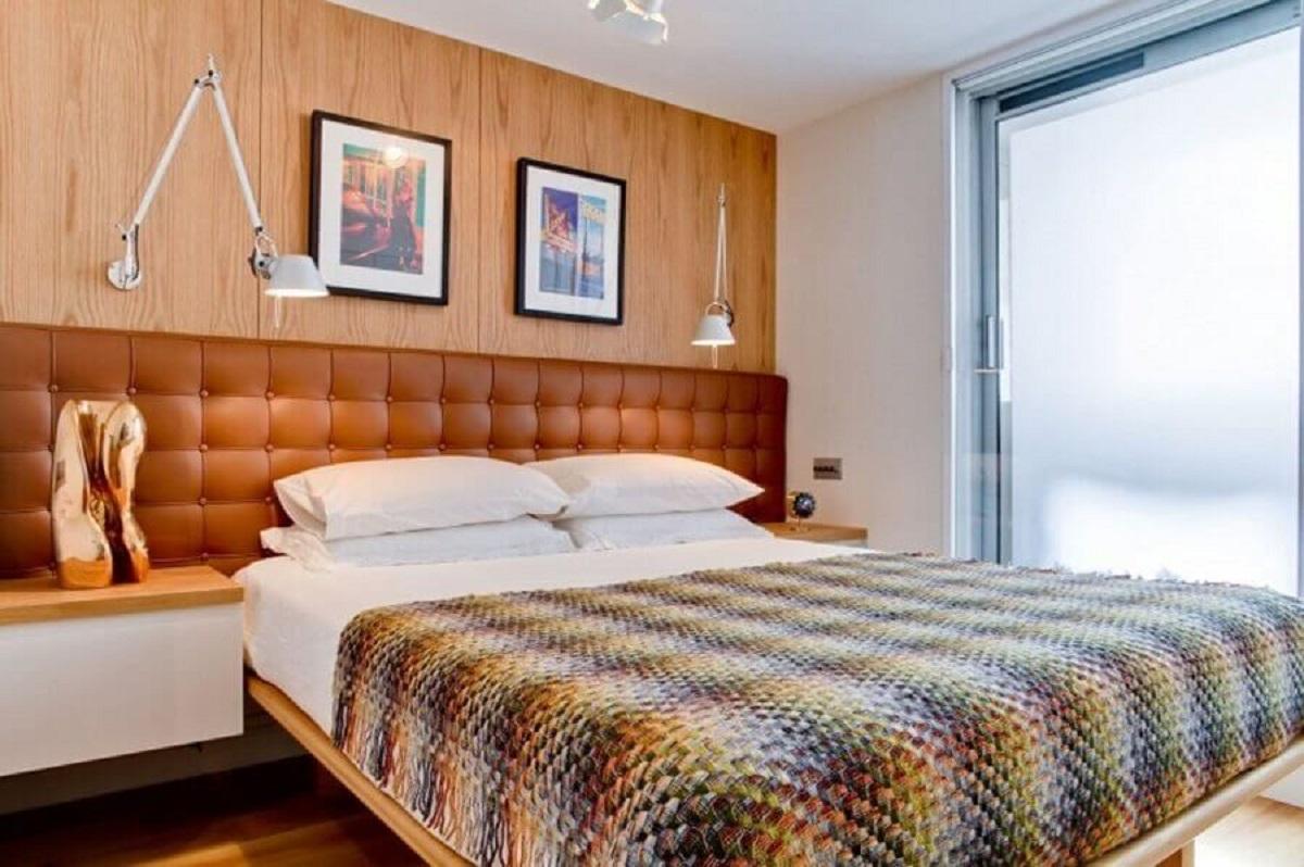 ideias para quarto de casal decorado com cabeceira de couro e revestimento de madeira Foto HomeDSGN