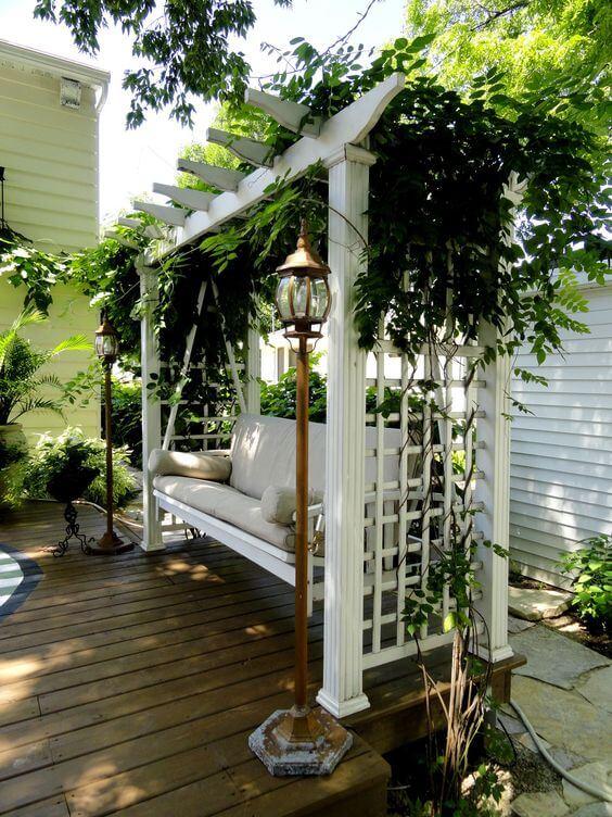 Jardim com banco de balanço branco decorado com Flores