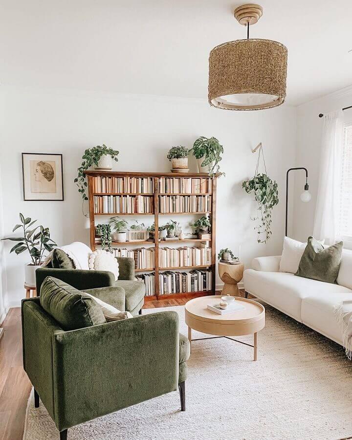 luminária de teto para sala de estar clean decorada com estante de livros e poltrona verde Foto Apartment Therapy