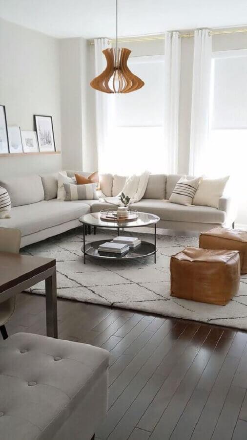 luminária de teto para sala de estar clean decorada com puff de couro e sofá de canto Foto Decoholic