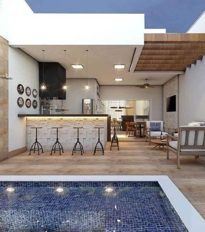 modelos de área gourmet com piscina decorada com poltronas de madeira Foto Julia Azan