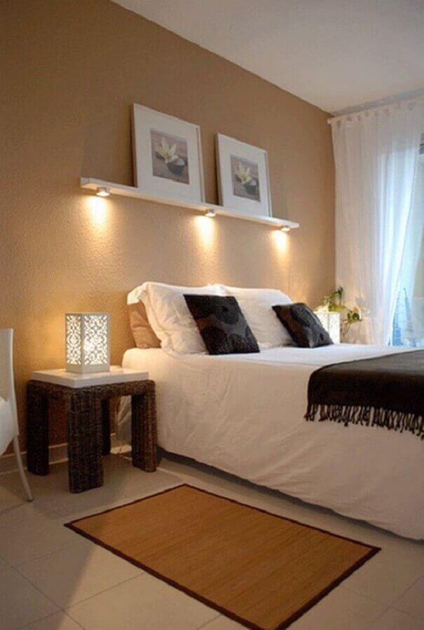 Quarto de casal simples e bonito decorado na cor bege com prateleira com iluminação e piso bege