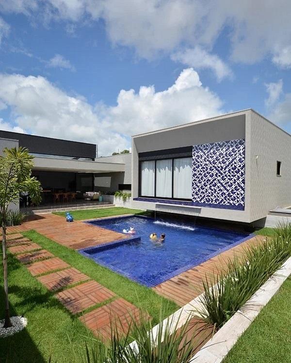 Revestimento de parede externa em cerâmica com nuances de azul e branco que se misturam ao tom da piscina. Fonte: Giordano Rogoski