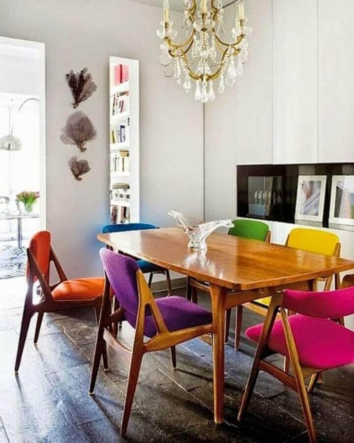 sala branca decorada com mesa de madeira e cadeira de jantar colorida Foto Archidea