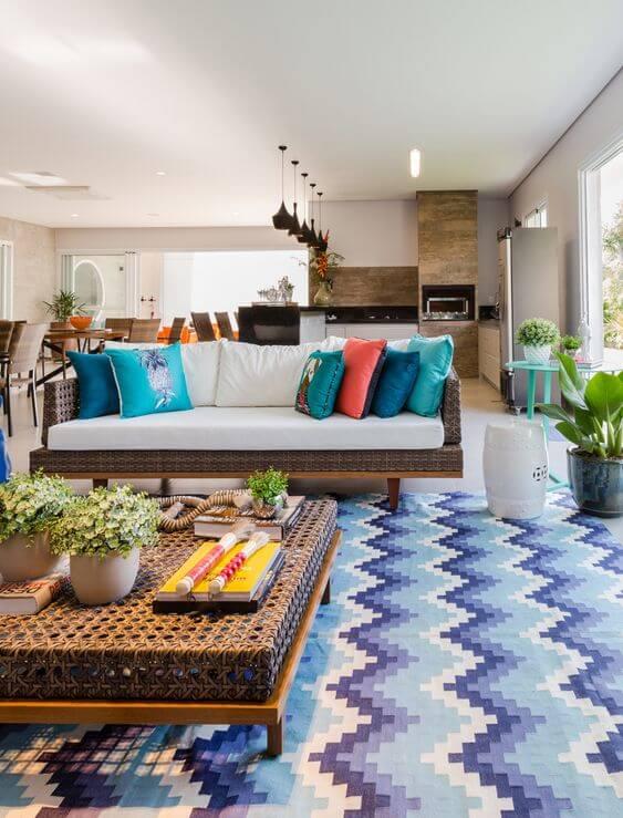 Sala com tapete chevron em tons de azul e almofadas laranja