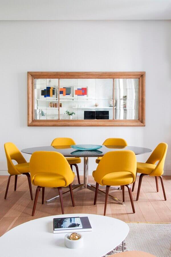 sala de jantar clean decorada com espelho de parede e cadeira de jantar estofada amarela Foto Behance