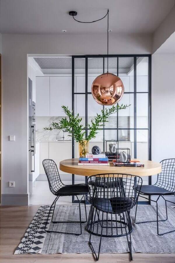 sala de jantar decorada com mesa de madeira e luminária pendente redonda rose gold Foto Fashionismo
