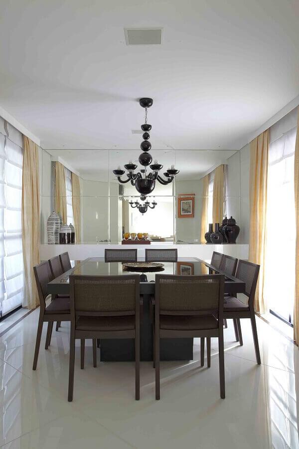 sala de jantar decorada com mesa quadrada e lustre de teto preto Foto Otimizi