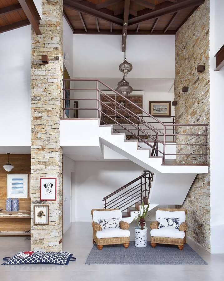 sala de visita decorada com revestimento de parede rústico e escadas internas em U Foto RBP Arquitetura e Interiores