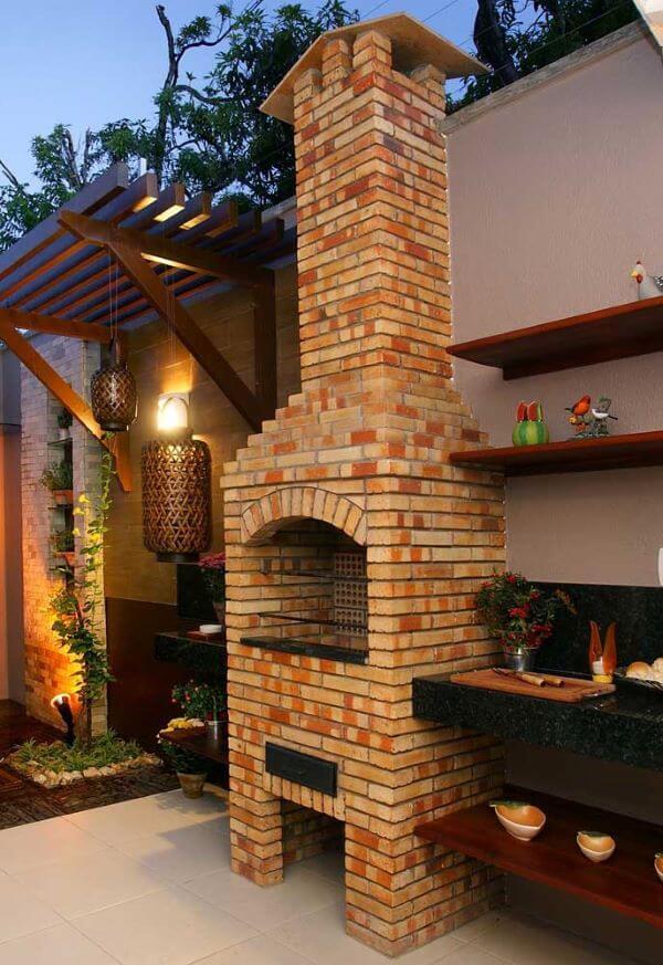 Área externa com churrasqueira pequena de tijolinho e chaminé