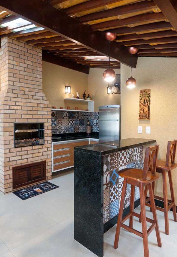 Área gourmet planejada com churrasqueira de tijolinho pequena e chaminé acima do telhado
