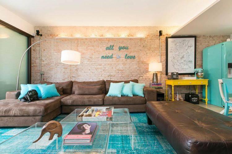 Sala com papel de parede de tijolinho e sofá de canto marrom