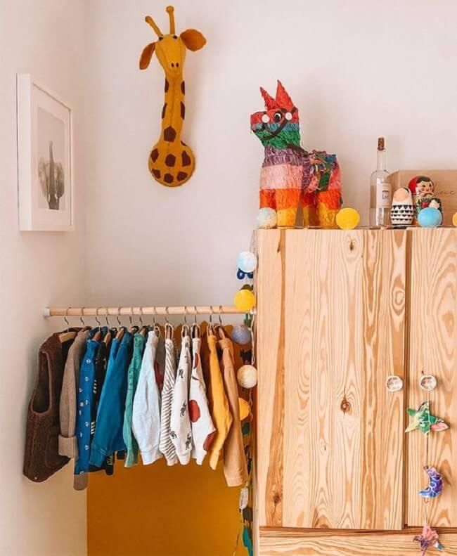 A arara de madeira para quarto montessoriano normalmente fica na altura das crianças. Fonte: Pinterest