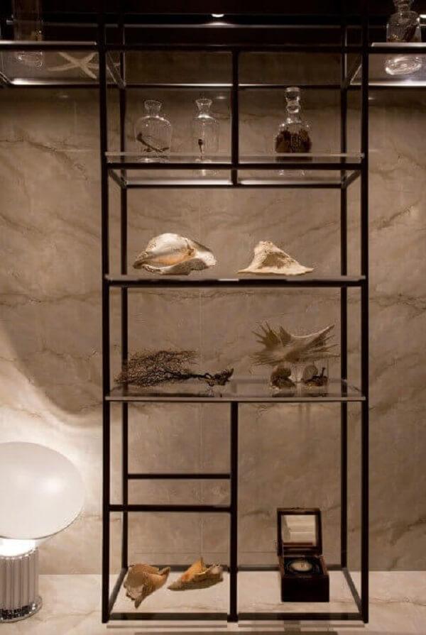 A estante de vidro pode ser usada em diferentes cômodos do imóvel. Projeto de Sandra Moura