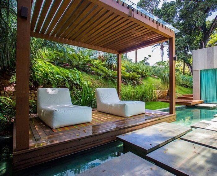 A poltrona divã embaixo do pergolado traz ainda mais conforto aos usuários da piscina. Fonte: Sidney Quintela Architecture