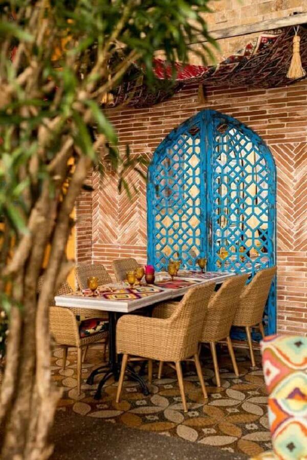 A porta vazada em azul turquesa reforça a decoração indiana na área externa. Fonte: Pinterest