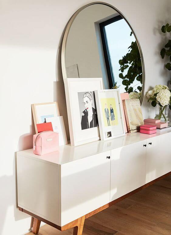 Aparador retro decorado com moldura redonda para espelho
