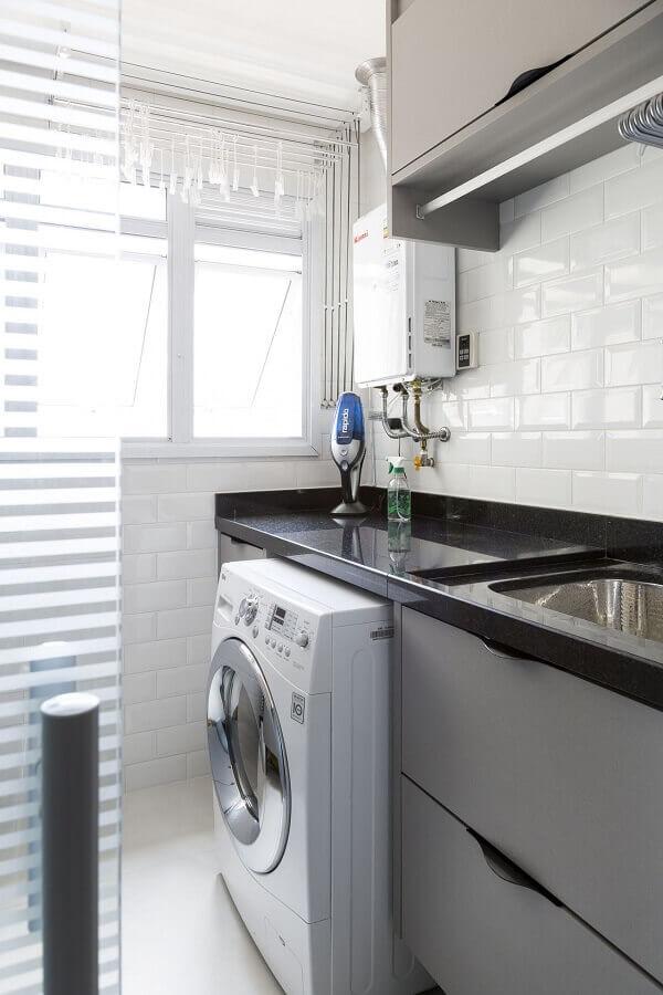Bancada de granito preto e revestimento de cerâmica branco decoram a lavanderia. Fonte: Bárbara Dundes