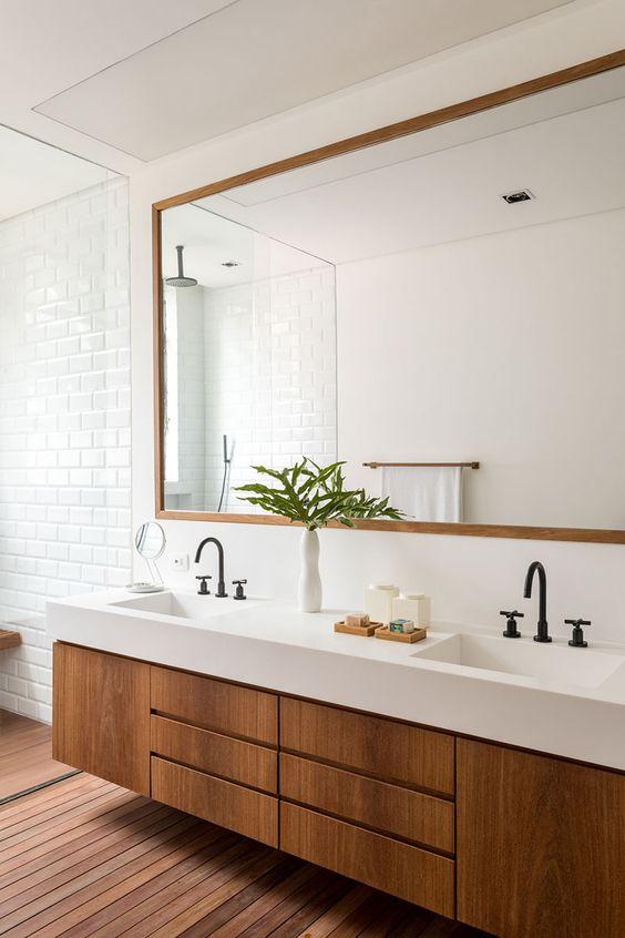 Banheiro com armário de madeira com silestone branco