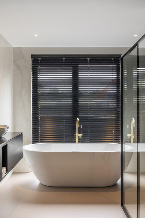 Banheiro com banheira e persiana preta