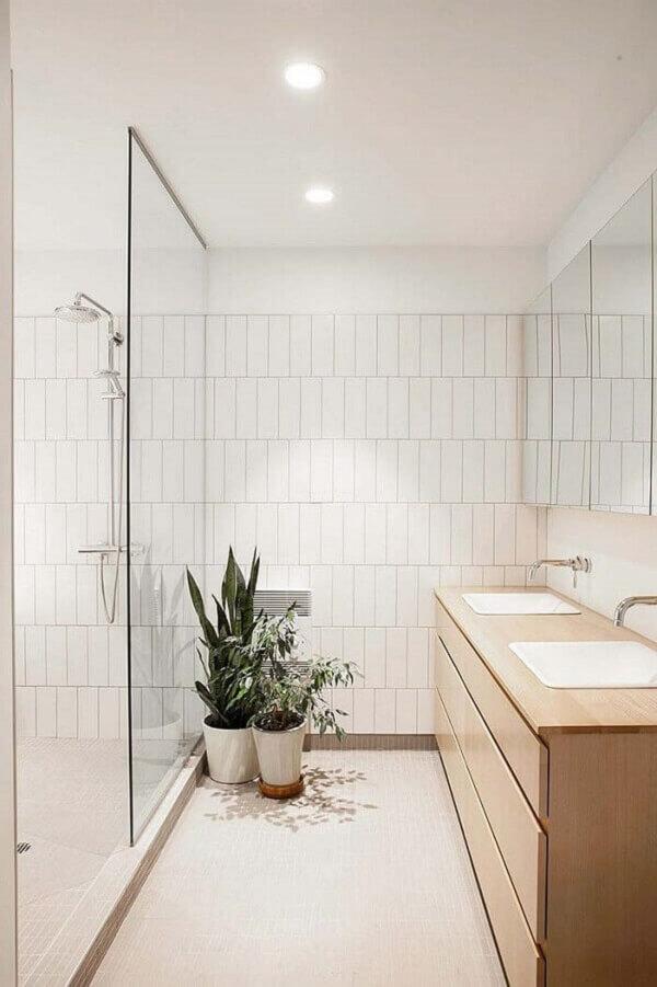 Banheiro com gabinete de madeira e revestimento cerâmico branco. Fonte: HomeDeco
