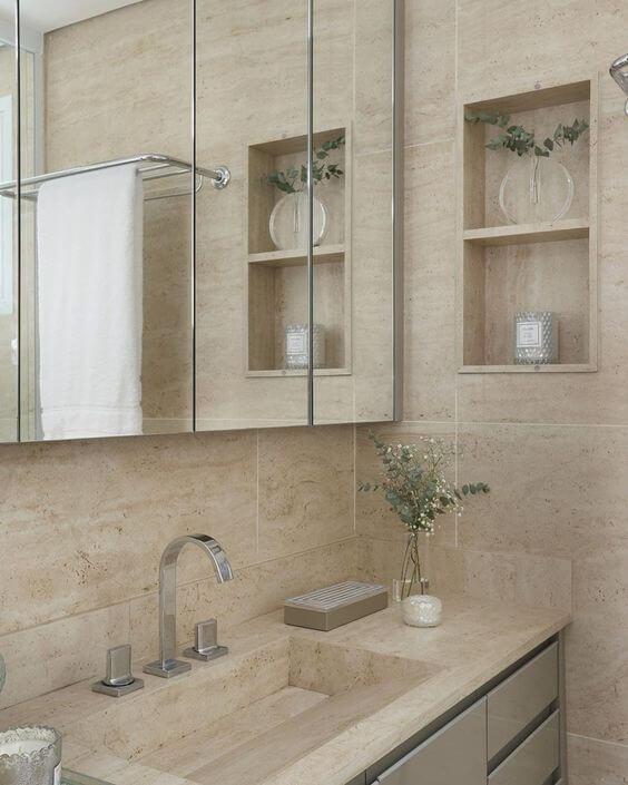 Banheiro com revestimento bege e nicho de embutir perto da espelheira