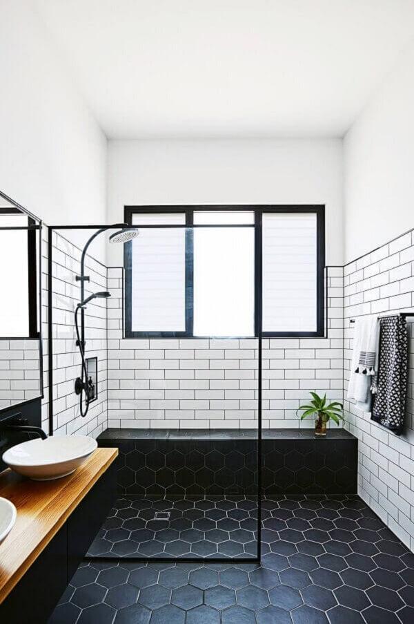 Banheiro minimalista com piso preto hexagonal e revestimento cerâmico branco. Fonte: Pinterest